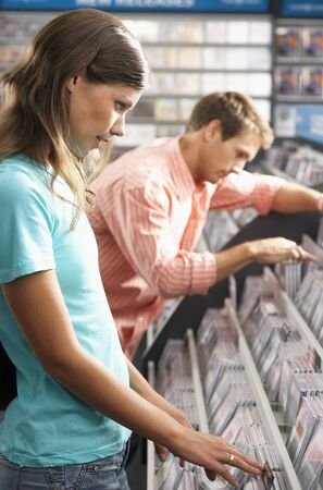 merchandise: Young couple choosing CDs in record shop, side view