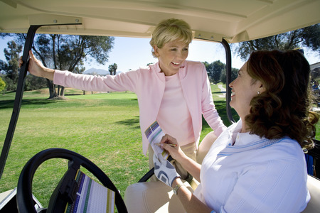 filling out: Two mature women playing golf, brunette sitting in golf buggy, filling out scorecard, blonde standing beside buggy, smiling LANG_EVOIMAGES