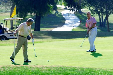 mature men: Two mature men playing golf, man playing putting stroke on green, second man holding flag, watching LANG_EVOIMAGES