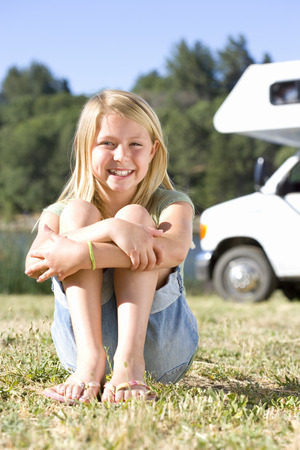 motor home: Girl (9-11) on grass with knees to chest, motor home in background, smiling, portrait
