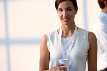 sleeveless top: Woman in white sleeveless top holding disposable cup, smiling, front view, portrait