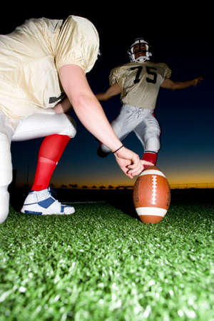 level playing field: American football player attempting to kick field goal, teammate holding ball vertically against pitch at sunset (surface level)