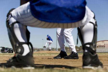 level playing field: Baseball batter facing pitcher during competitive game, view through catcher's legs, rear view, focus on background LANG_EVOIMAGES