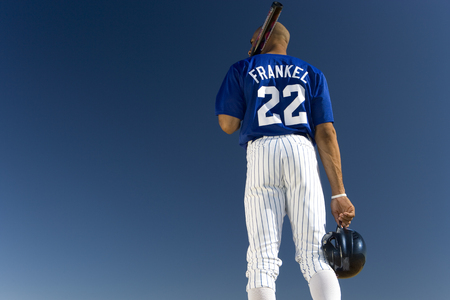 facing away: Baseball player standing against clear blue sky, carrying bat on shoulder, rear view, low angle view LANG_EVOIMAGES