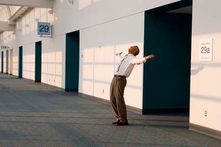 business profiles: Joyous businessman standing outside meeting room, arms out and head back, smiling, side view