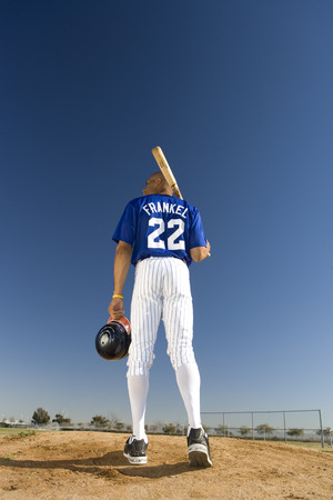 facing away: Baseball player standing on pitch, carrying bat on shoulder, rear view (surface level)