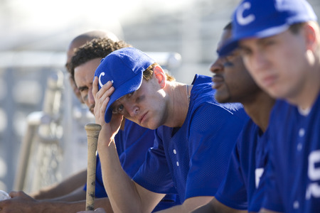 baseball sport: Dejected baseball team, in blue uniform, sitting on bench in stand during competitive baseball game, side view (differential focus) LANG_EVOIMAGES