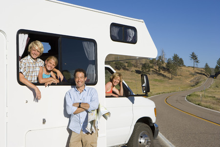 motor home: Family of four with motor home, man with map by son and daughter (8-12), mother looking out of window, smiling, portrait