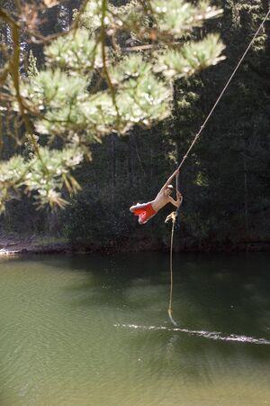 swimming shorts: Boy (9-11), in swimming shorts, swinging on rope above lake