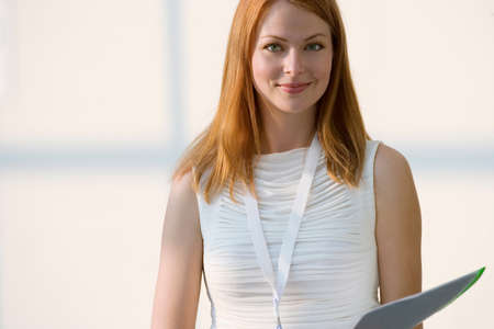 sleeveless top: Woman in white sleeveless top holding folder, smiling, front view, portrait LANG_EVOIMAGES