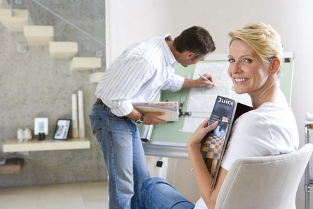 rewarding: Man writing on blue print on drafting board, woman smiling in foreground
