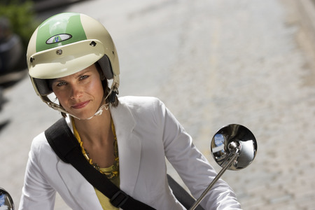 crash helmet: Woman in crash helmet riding on scooter in street, smiling, front view, close-up, portrait (tilt) LANG_EVOIMAGES