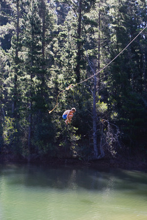 only one teenage boy: Boy (8-10), in swimming shorts, letting go of rope swing above lake, hugging knees, side view