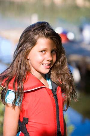 life jacket: Girl (7-9) wearing red life jacket, smiling, portrait