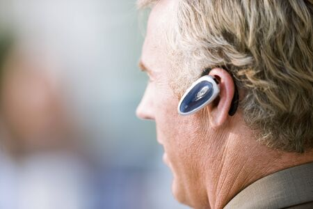 handsfree device: Mature businessman wearing mobile phone hands-free device, close-up, profile LANG_EVOIMAGES