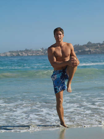 swimming shorts: Man in swimming shorts standing on leg on sandy beach by waters edge, stretching, front view