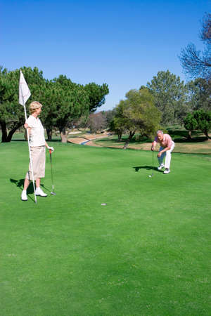 lining up: Mature couple playing golf, man lining up golf shot on putting green, woman holding flag