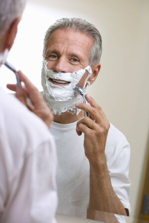differential focus: Senior man shaving at home, using razor and shaving foam, reflection in bathroom mirror, smiling, rear view, portrait (differential focus) LANG_EVOIMAGES