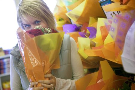 only mid adult women: Woman smelling flower bouquet beside shop display in florists, face obscured, portrait