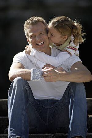man front view: Girl (9-11) embracing father sitting on steps, kissing man on cheek, smiling, front view