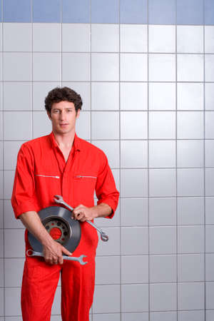 vehicle part: Male car mechanic, in red overalls, standing in auto repair shop near tiled wall, holding vehicle part and wrenches, smiling, portrait LANG_EVOIMAGES