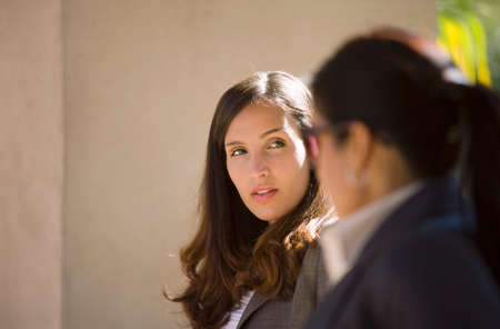 differential focus: Two businesswomen having meeting outdoors, side view (differential focus)