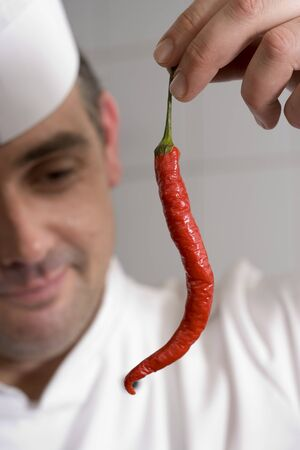 differential focus: Male chef examining single red chilli pepper in commercial kitchen, smiling, close-up (differential focus)