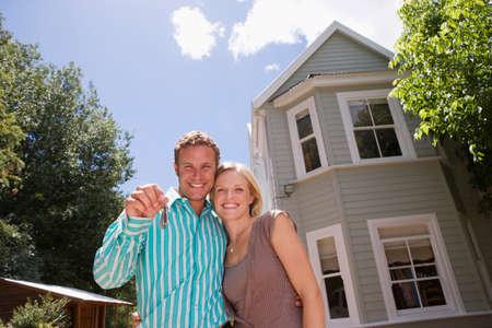 holding aloft: Couple standing in driveway in front of detached house, man holding aloft set of keys, smiling, portrait LANG_EVOIMAGES