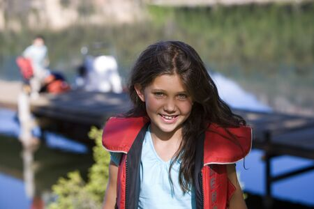 life jacket: Girl (7-9) standing near lake jetty, wearing red life jacket, smiling, front view, portrait