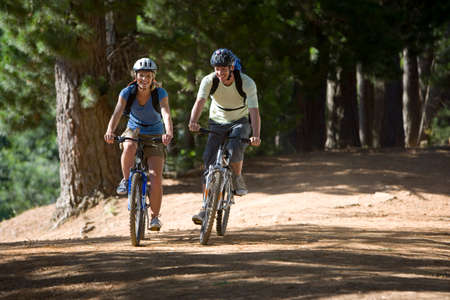 rucksacks: Couple, with rucksacks and cycling helmets, mountain biking along woodland trail, smiling, front view