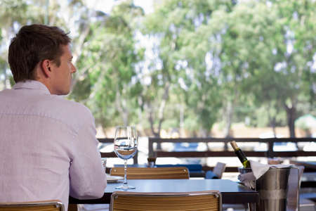 stood up: Man sitting at table on restaurant balcony with glass of wine and ice bucket, rear view