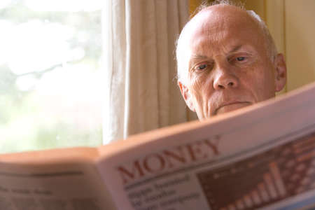 financial reward: Senior man reading newspaper, close-up