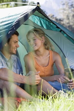 differential focus: Young couple sitting in dome tent, holding camping mugs, smiling (differential focus)