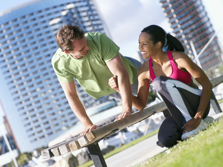 Couple exercising in park, man doing press-ups on bench, woman offering encouragement, smiling (tilt) Imagens