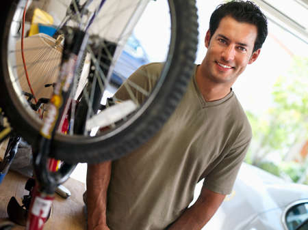 domestic garage: Man repairing bicycle on workbench in domestic garage, smiling, portrait (tilt) LANG_EVOIMAGES