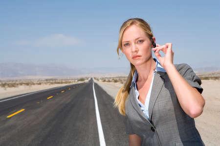 earpiece: Businesswoman on side of road in desert, hand on earpiece, portrait, close-up