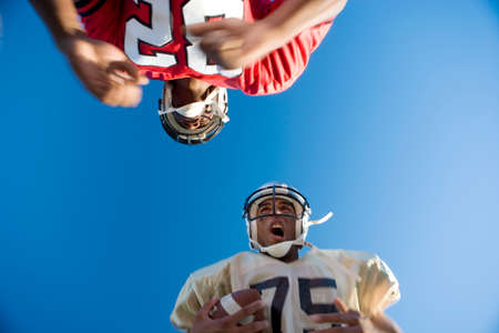 opposing: American football player running with ball at opposing player during competitive game, upward view