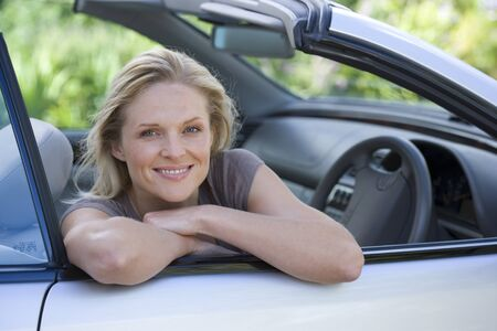 only mid adult women: Woman sitting in driving seat of parked convertible car on driveway, smiling, side view, portrait LANG_EVOIMAGES