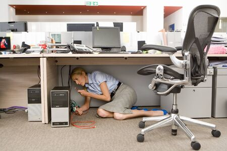underneath: Businesswoman fixing computer under desk in office