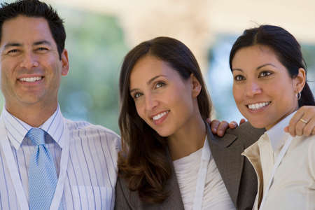 Two businesswomen and businessman standing with arms around each other, smiling Stock Photo