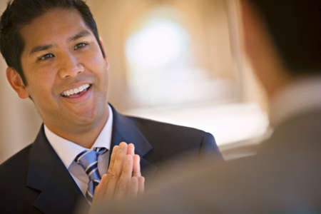 differential focus: Respectful businessman greeting counterpart in building arcade, smiling (differential focus, tilt) LANG_EVOIMAGES