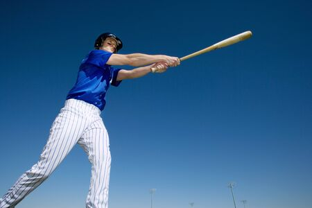 tilt view: Baseball batter, in blue uniform, hitting ball during competitive game, side view, low angle view (tilt) LANG_EVOIMAGES