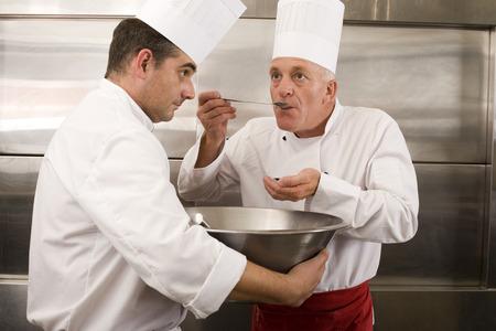 요리사 큰 스푼으로 두 번째 요리사 맛 음식 샘플, 상업 부엌에 큰 그릇을 들고