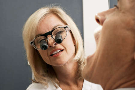 differential focus: Female dentist wearing surgical loupes, examining patient, close-up (differential focus)
