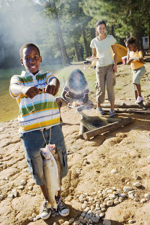 holding aloft: Family cooking food on camping trip beside lake, boy (8-10) holding aloft fish in foreground, smiling, portrait