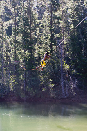 swimming shorts: Man, in yellow swimming shorts, swinging on rope above lake, side view