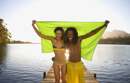 lake front: Couple standing on lake jetty, arms around each other, holding aloft green towel, smiling, front view, portrait LANG_EVOIMAGES
