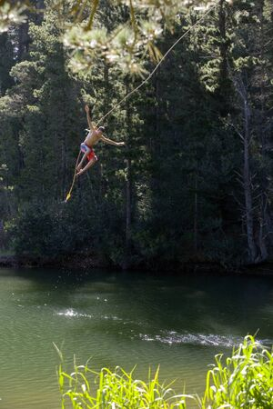 swimming shorts: Boy (9-11), in swimming shorts, letting go of rope swing above lake