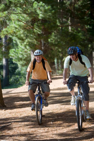 rucksacks: Senior man and adult son, with cycling helmets and rucksacks, mountain biking along woodland trail, smiling, front view