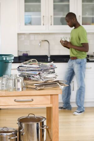 differential focus: Young man rinsing jars in kitchen by newspapers, empty jars and cans for recycling on side (differential focus)